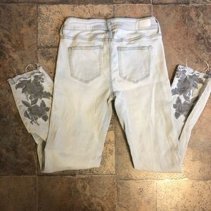 Bleached distressed embroidered hem jeans